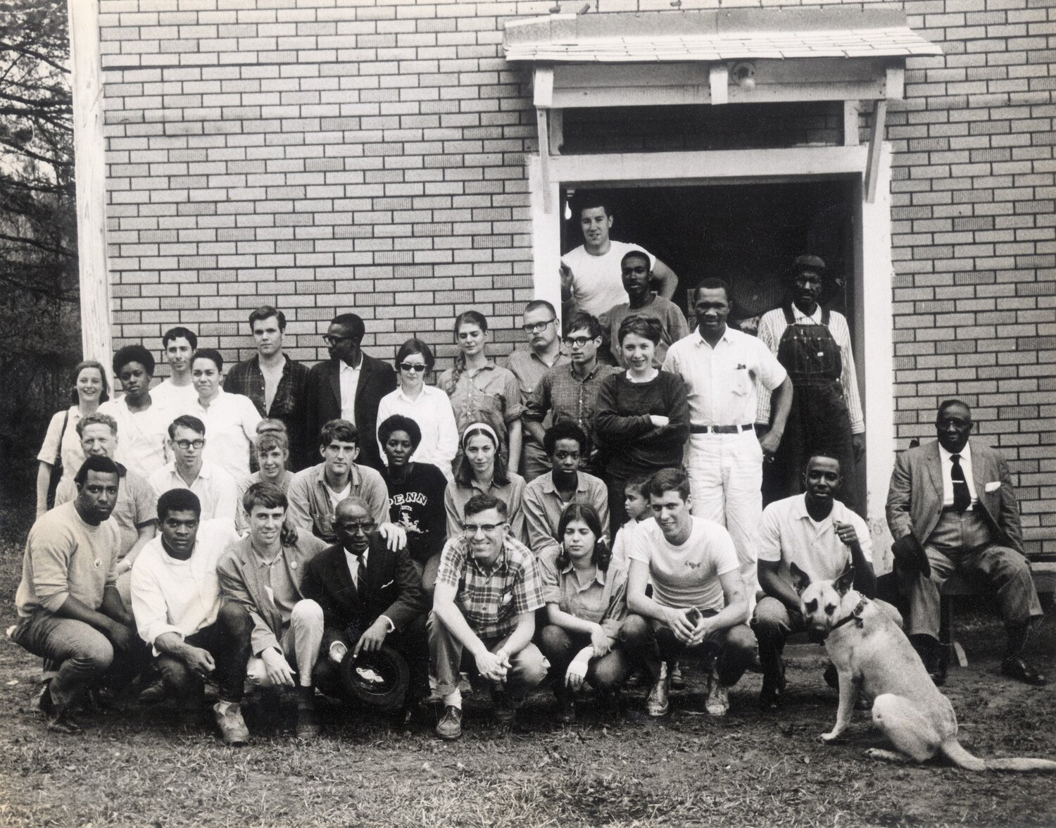 CORE volunteers, workers and local activists gather to rebuild Pleasant Grove Baptist Church in Jonesboro, La., one of the two black churches destroyed by arsonists in January 1965. The Deacons protected college student volunteers who aided the rebuild project. Shown are, front row, left to right, Alvin Culpepper; unidentified volunteer; Charlie Fenton, CORE; the Rev. E. H. Houston, church pastor); and Duffy, Fenton's dog. Second row, fifth from left, Cathy Patterson, CORE. Top row, fourth from left, Ronnie Moore, CORE. In the doorway, left to right, Mike Lesser, CORE, and Jonesboro residents Eddie Scott, Lee Gilbert and Freeman Knox.   Courtesy of the Ronnie Moore Papers, Amistad Research Center, New Orleans, La.